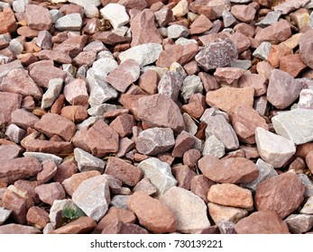 Red and white rocks of different shapes and sizes in a garden