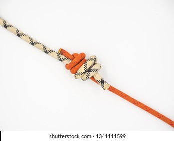 Red and white ropes connected by knot. Double fisherman's (also known as Grapevine or Double Englishman's) knot isolated on white.