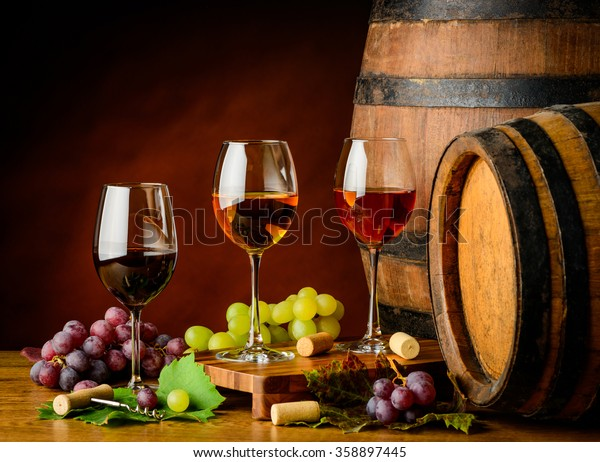 Red, white and rose wine in wine glass with grapes and barrel decor