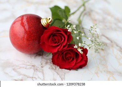 Red and white roses with beautiful glittery Christmas ornaments. Photographed on a white marble surface. Still Life Photos with Christmas / Holiday season theme.