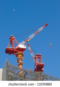 Red and white steel crane at a high rise building site in the city with the moon overhead and a blue sky background