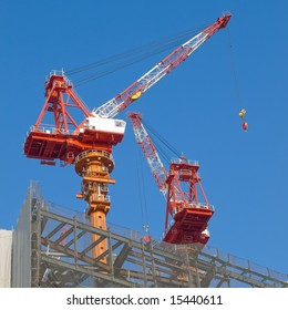 Red and white steel crane at a high rise building site