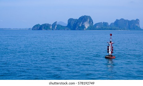 A red and white steel navigational floating buoy in the blue sea water, drift with the sea wave, among the wide ocean with giant island hill and blue sky, for anchored