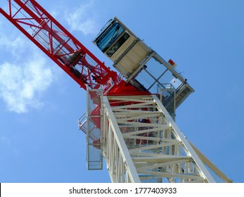 Red and white steel truss tower crane boom and vertical tower body under blue sky. truss structure and horizontal beam. operator cabin attached on the side. construction concept. low angle view.