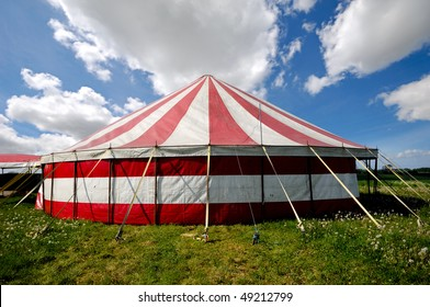 A red and white striped circus tent in green nature. The sky is blue with white cumulus clouds