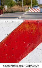 Red and white striped concrete road barrier - close up.