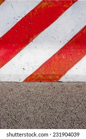 Red and white striped concrete road barrier on asphalt - close up.