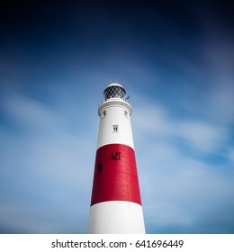 Red and white striped lighthouse against a blue sky