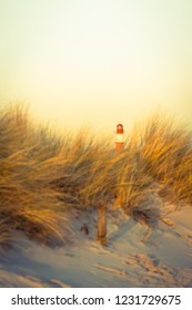 Red and white striped lighthouse in bright sunny evening light at distant horizon, seen from beach grass dune (copy space)