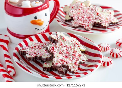 Red and white striped plate filled with snowflake shaped chocolate peppermint bark candies with snowman mug filled with hot chocolate