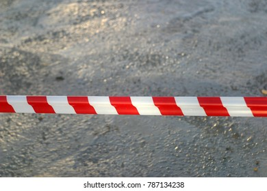 Red and white, striped protective tape protects fresh cement, repair work. Industrial artistic background