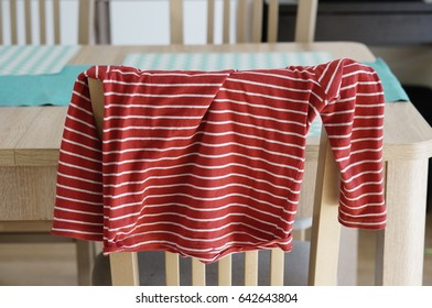 Red white striped shirt hanging on wooden chair