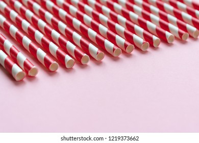 Red and White striped straws. Pink background