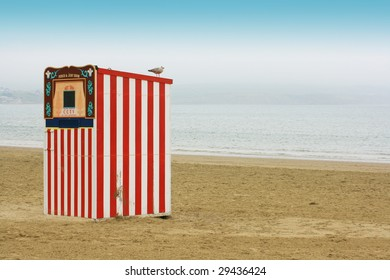 A red and white striped wooden punch and Judy booth on a beach located in Weymouth, Dorset UK.  A seagull perches on top. landscape format, room for copy space etc.