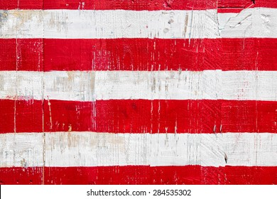 Red and white stripes hand painted on planks of rustic reclaimed wood. Background for July 4th, Memorial Day, Veterans Day, Labor Day or other patriotic occasion.