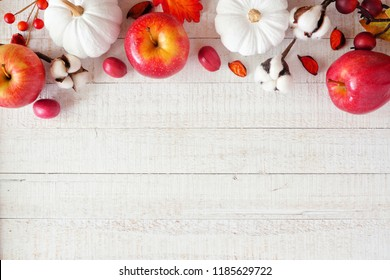 Red and white theme autumn top border with apples and pumpkins on a white wood background. Copy space.