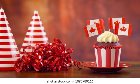 Red and white theme cupcakes with Canadian maple leaf flags for first of July Canada Day or Canadian theme party food.