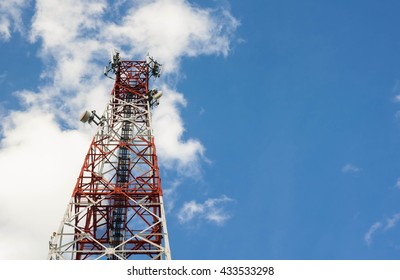 Red and white tower of communications with with a lot of different antennas under blue sky