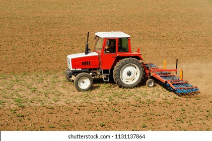 Red and white tractor with a hoe tiller cultivator machine as trailer on a land field with little plants