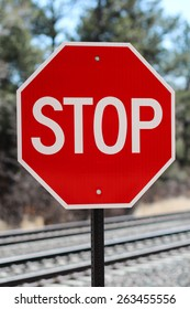 Red And White Traffic Stop Sign Placed Near Train Tracks In Colorado Springs, Colorado Against Forest Background
