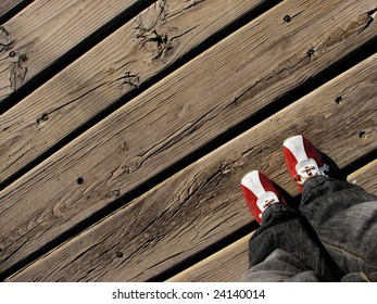 Red and white trainers - training shoes on a wooden floor on the beach in a sunny day