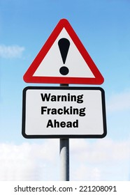 A red and white triangular road sign with a warning about the dangers of Fracking ahead concept against a partly cloudy sky.