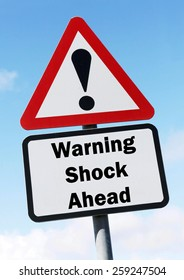 Red and white triangular road sign with a warning of Shock ahead concept against a partly cloudy sky background