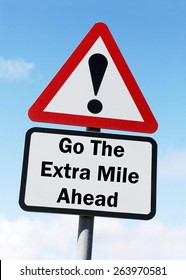 Red and white triangular road sign with a warning to Go the Extra Mile ahead concept against a partly cloudy sky background