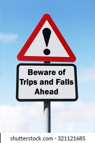 Red and white triangular road sign with warning to Beware of Trips and Falls ahead concept against a partly cloudy sky background