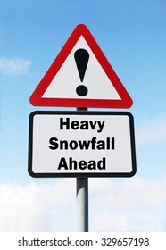 Red and white triangular road sign with a warning of Heavy Snowfall Ahead concept against a partly cloudy sky background