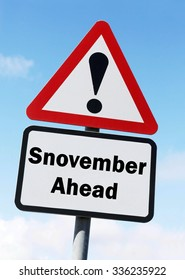 Red and white triangular road sign with a warning of Snovember Ahead play on words concept against a partly cloudy sky background