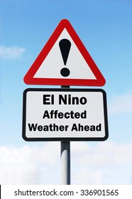 A red and white triangular road sign with a warning of a El Nino Affected Weather Ahead concept against a partly cloudy sky.