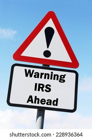 Red and white triangular warning road sign with a warning of the IRS ahead concept against a partly cloudy sky background