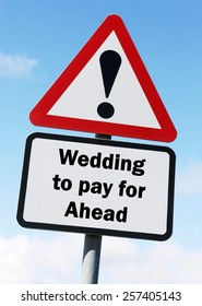 Red and white triangular warning road sign with a warning of a Wedding to Pay For ahead concept against a partly cloudy sky background