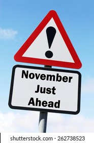 Red and white triangular warning road sign informing that November is Just Ahead concept against a partly cloudy sky background