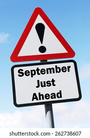 Red and white triangular warning road sign informing that September is Just Ahead concept against a partly cloudy sky background