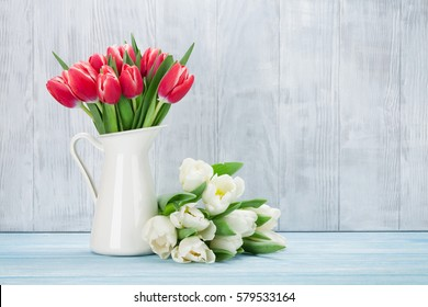 Red and white tulips bouquet in front of wooden wall. With space for your text
