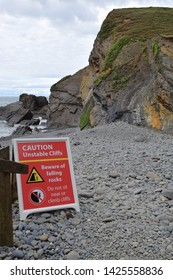 Red and white warning sign on pebble beach regarding the unstable cliff with sea, sky and rocks in background