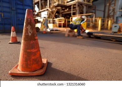 Red and white warning witches hat traffic sign corn barrier applying exclusion zone to ensure stopping public safety entering while miner undertaking gouging metal plate construction mine site, Perth