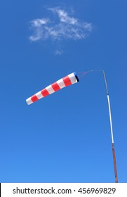 Red and white windsock made of fabric hangs almost horizontally on a pole against a blue sky with a slight cloud