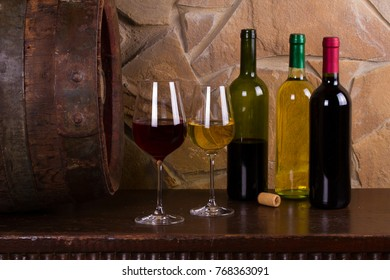 Red and white wine beside old cask in wine cellar