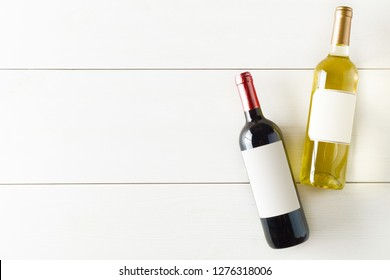 Red and white wine bottle on white wooden table flat lay from above with copy space