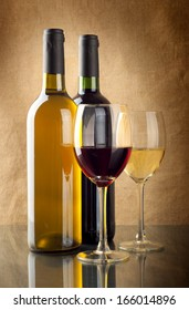 Red and white wine in bottles and wineglasses on linen background