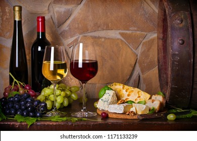 Red and white wine with cheese and grapes beside old cask in wine cellar. Glasses and bottles of wine