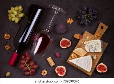 Red and white wine with cheese plate. Wine glasses with cheese,  grapes, figs and nuts on black background. Wine and food concept. View from above, top, horizontal