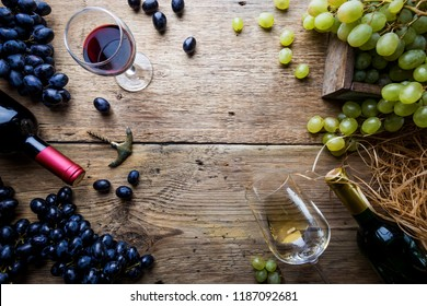 Red and white wine with glass, bottle and grapes over wooden background, copy space , top view.