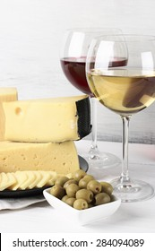Red and white wine in glasses and assorted cheese with olives on rustic wooden background.