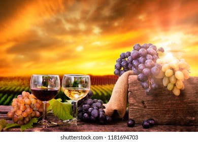 Red and white wine in glasses with fresh grapes on the wooden table