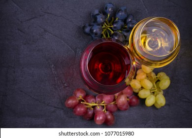 Red and white wine in wine glasses with grapes on dark stone background with copy space. overhead