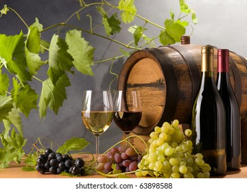 Red and White wine with grapes and a wine barrel